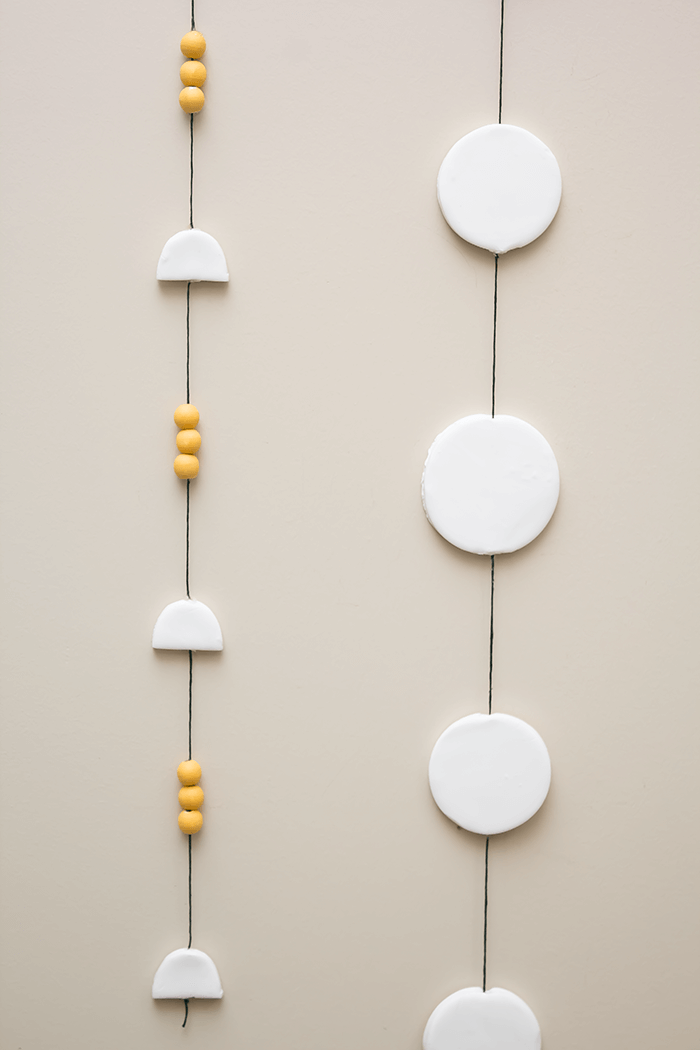 Add a touch of whimsy to your walls with these modern DIY clay and wood bead mobiles (using polymer clay).